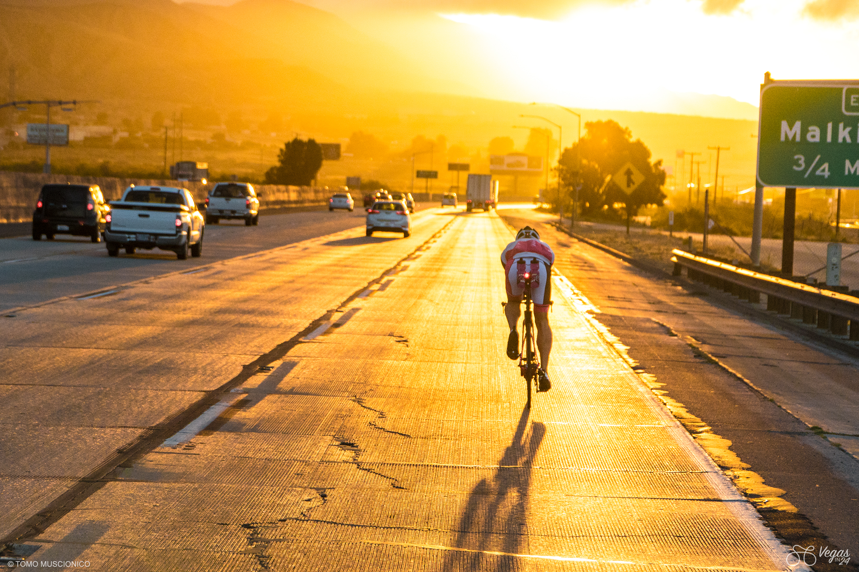 As Andy Funk rides his bike on the I-10 freeway for the less than 10 allowable miles of the event, the streets are painted in gold by the rising sun.