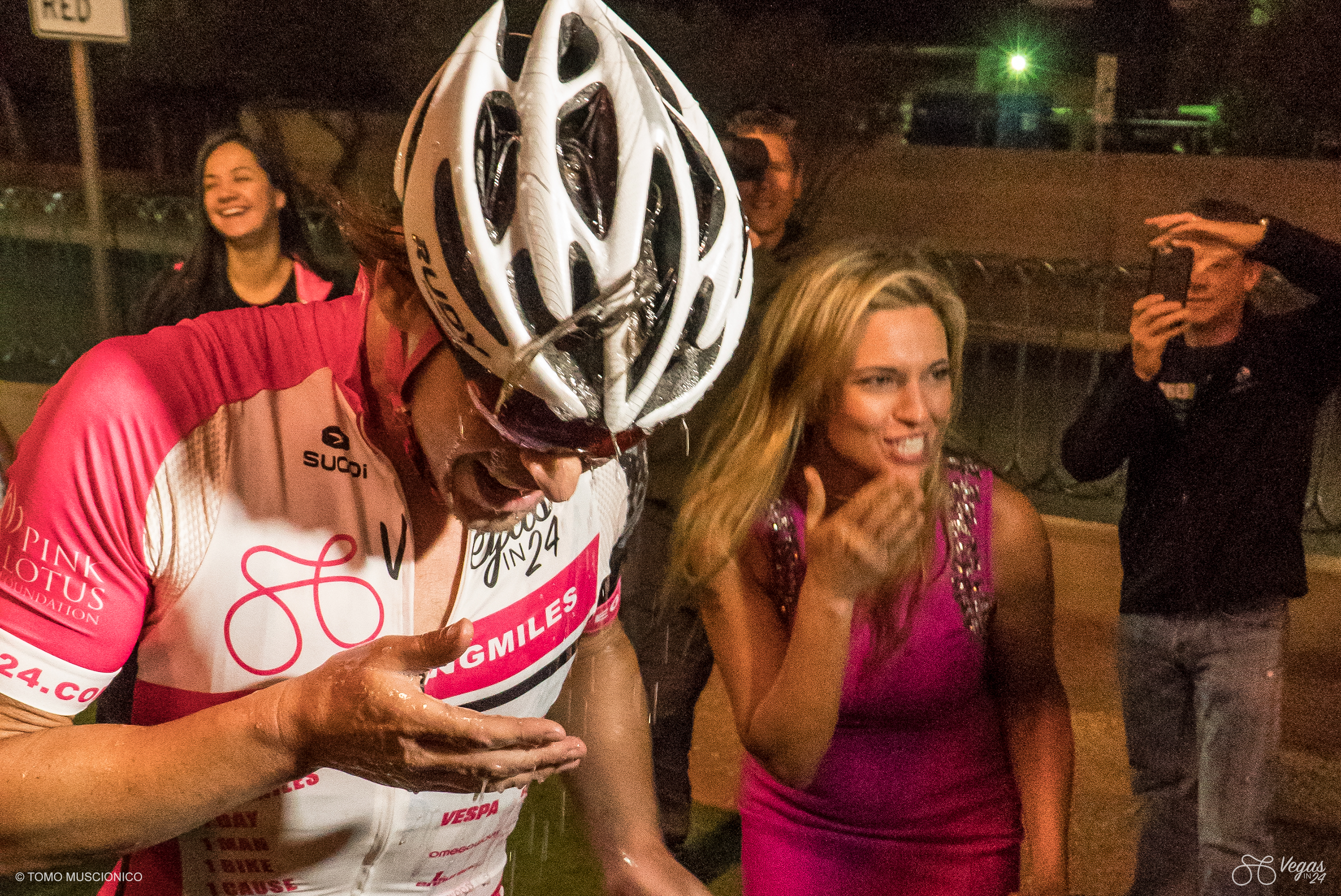 After 365 miles and 20:41:25 grueling hours in the saddle, Kristi Funk surprises Andy Funk with a champagne shower at the finish line in Las Vegas.